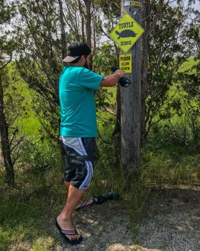Chris Leone mounting a turtle crossing sign